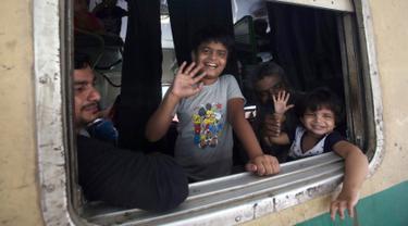 Anak-anak melambaikan tangan saat berada di kereta sebelum berangkat ke kampung halaman mereka untuk liburan Idul Fitri di stasiun kereta api di Karachi, Pakistan (2/6/2019). Idul Fitri menandai akhir bulan suci Ramadan. (AP Photo/Fareed Khan)