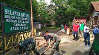 TNI bersama Tim Sar gabungan membersihkan tumpukan lumpur yang terbawa arus banjir di kawasan Situs Sunan Kalijaga di Cirebon. Foto (Liputan6.com / Panji Prayitno)