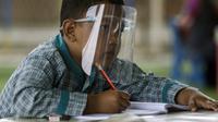Siswa SD memkai pelindung wajah saat pembelajaran tatap muka di Sekolah Islam Ibnu Aqil Ibnu Sina, Soreang, Bandung, Jawa Barat, Rabu (5/8/2020). Indonesia akan mengizinkan sekolah di zona hijau COVID-19 melakukan pembelajaran tatap muka di bawah protokol kesehatan yang ketat. (Xinhua/Septianjar)