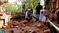 Pemuka agama memantau kerusakan pada bagian candi yang runtuh akibat gempa di Pura Lokanatha, Denpasar, Bali, Selasa (16/7/2019). Gempa Magnitudo 5,8  yang mengguncang Bali tidak menimbulkan korban jiwa, tapi sejumlah bangunan di beberapa kawasan mengalami kerusakan. (AP/Firdia Lisnawati)