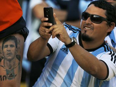 Seorang fan memotret tato Lionel Messi di Cile. (Reuters/Ivan Alvarado)