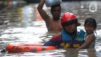 Petugas Pemadam Kebakaran mengevakuasi anak-anak korban banjir dengan menggunakan ban di kawasan Karet Pasar Baru Barat, Jakarta, Selasa (25/2/2020). Banjir yang terjadi sejak subuh akibat luapan Kanal Banjir Barat tersebut merendam ratusan rumah hingga setinggi dua meter. (merdeka.com/Arie Basuki)