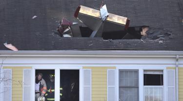 Pesawat ringan bermesin satu yang menabrak atap kondominium di Methuen, Massachusetts, (1/3). Dalam kejadian ini pilot pesawat tewas. (AP/Elise Amendola)