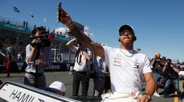 Pembalap dari tim Mercedes, Lewis Hamilton mengikuti parade jelang balapan pertama musim ini di GP F1 Australia di Melbourne, Australia, (25/3). Hamilton menempati posisi start terdepan dalam Grand Prix Australia. (AP Photo/Asanka Brendon Ratnayake)