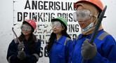 Foto pada 26 Januari 2019 menunjukkan seorang mahasiswa, Genta Kalbu Tanjung (kiri) bersama dua temannya setelah sesi permainan di Temper Clinic, Jakarta. Sesuai namanya, Temper Clinic memang memberikan tempat untuk menyalurkan amarah. (GOH Chai Hin/AFP)
