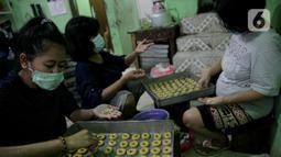 Pekerja menyelesaikan pembuatan kue kering di sebuah industri rumahan di Kawasan Kwitang, Jakarta, Jumat (30/4/2021). Kue kering tersebut dijual mulai harga Rp 75.000 hingga Rp. 80.000 per kilogram tergantung jenis dan variannya. (Liputan6.com/Faizal Fanani)