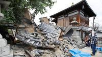 Gerbang Kuil Myotoku-ji runtuh setelah gempa bumi melanda Kota Ibaraki, Osaka, Jepang, Senin (18/6). Kyodo News Agency melaporkan bahwa seorang gadis cilik  dan lansia tewas tertimpa reruntuhan. (Yosuke Mizuno/Kyodo News via AP)