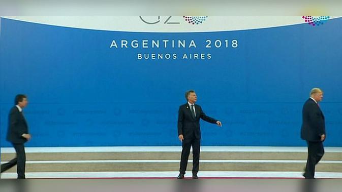 Presiden AS Donald Trump (kanan) meninggalkan Presiden Argentina Mauricio Macri (tengah) di panggung foto bersama KTT G20 (1/12) (POOL / Screengrab by Daily Mail)