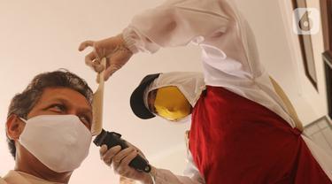 Tukang cukur mengenakan APD saat memotong rambut di halaman rumah pelanggan, Kelapa Dua, Depok, Jawa Barat, Senin (27/4/2020). Penerapan PSBB Kota Depok membuat tukang cukur tersebut menerima jasa panggilan ke rumah dan mengenakan APD untuk mencegah penularan COVID-19. (Liputan6.com/Herman Zakharia)