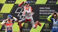 Pembalap Spanyol, Jorge Lorenzo (tengah) melompat merayakan selebrasi didampingi posisi kedua pembalap Marc Marquez dan posisi ketiga Valentino Rossi usai balapan MotoGP Catalunya di Sirkuit Catalunya, Montmelo, (17/6). (AFP PHOTO / Lluis Gen)