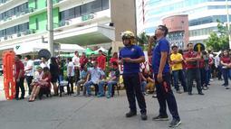 Pegawai kantor berkumpul di luar gedung setelah gempa bumi dahsyat  di Kota Davao, Filipina (29/10/2019). Lokasi gempa berada dekat Kota Kisante dan kurang dari 100 kilometer (60 mil) dari Kota Davao. Pada kedalaman Sekitar 50 kilometer (30 mil). (AP Photo)