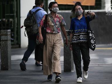 Dua wanita berjalan mengenakan masker pelindung untuk menghindari polusi udara buruk di Jakarta, Rabu (17/7/2019). Dinkes DKI menyarankan masyarakat untuk menggunakan masker saat beraktivitas untuk mencegah dampak polusi udara pada tubuh. (Liputan6.com/Faizal Fanani)