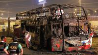 Petugas kepolisian berdiri dekat kerangka sebuah bus bertingkat yang hangus terbakar di terminal bus antarprovinsi, kota Lima, Peru, Minggu (31/3) malam. Sedikitnya 20 orang tewas dan belasan lainnya terluka dalam peristiwa nahas tersebut. (Photo by Luka GONZALES / AFP)