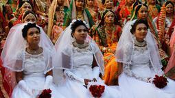 Ratusan pengantin duduk bersama saat nikah massal di Surat, India, Minggu (23/12). Mahesh Savani  telah mendanai pernikahan anak-anak yatim di Kota Surat selama beberapa tahun. (AP/Ajit Solanki)