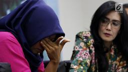 Terpidana kasus pelanggaran UU ITE Baiq Nuril (kiri) tertunduk sambil memegangi matanya saat berbicara dalam diskusi Dialektika Demokarasi di Kompleks Parlemen Senayan, Jakarta, Rabu (10/7/2019). Baiq berurai air mata saat berbicara di hadapan wartawan dan anggota dewan. (Liputan6.com/JohanTallo)