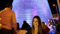 Caroline Chaptini berpose di depan Pohon Natal raksasa yang terbuat dari botol plastik di kota Chekka, Lebanon, 15 Desember 2019. Tujuan proyek ini adalah untuk memecahkan Guinness World Record sebelumnya, yakni pohon Natal yang dibangun dari 98.000 botol di Meksiko. (Ibrahim CHALHOUB/AFP)