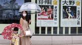 Warga yang mengenakan masker untuk melindungi diri dari penyebaran COVID-19 berjalan melewati laporan raihan medali emas Jepang di Olimpiade Tokyo 2020, Tokyo, Selasa (27/7/2021). Tokyo melaporkan jumlah kasus harian COVID-19 tertinggi beberapa hari setelah Olimpiade mulai. (AP Photo/Koji Sasahara)
