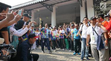 Gubernur DKI, Anies Baswedan membawa obor saat Pawai Obor Asian Para Games di Balai Kota DKI Jakarta, Minggu (30/9). Pawai obor dimulai dari Balai Kota dan berakhir di Gedung Kementerian Pemuda dan Olahraga (Kemenpora). (Liputan6.com/Herman Zakahria)