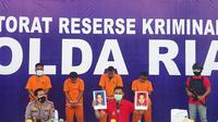 Direktur Reserse Kriminal Umum Polda Riau Kombes Zain Dwi Nugroho memperlihat dua buronan pelaku bom molotov di Kabupaten Kampar. (Liputan6.com/M Syukur)