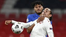 Pemain Inggris, Tyrone Mings, berebut bola dengan pemain Denmark, Yussuf Poulsen, pada laga UEFA Nations League di Stadion Wembley, Kamis (15/10/2020). Denmark menang dengan skor 1-0. (Daniel Leal-Olivas/Pool via AP)