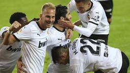 Para pemain tim Valencia melakukan selebrasi setelah mencetak gol ketiga tim mereka ke gawang Real Madrid pada lanjutan La Liga di Stadion Mestalla, Selasa (9/11/2020) dinihari WIB. Real Madrid kalah telak 1-4 dari tuan rumah Valencia. (AP Photo/Alberto Saiz)
