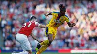 Aksi Wilfried Zaha melewati Sean Kolasinac pada laga lanjutan Premier League yang berlangsung di Stadion Emirates, Minggu (21/4). Arsenal kalah 2-3 kontra Crystal Palace. (AFP/Adrian Dennis)