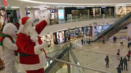 Petugas yang mengenakan kostum Sinterklas menyapa pengunjung di Senayan City Mall, Jakarta, Jumat (25/12/2020). Kegiatan tersebut bertujuan untuk melengkapi kebahagiaan Natal tahun 2020. (Liputan6.com/Herman Zakharia)