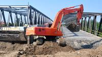 Sebuah alat berat menyelesaikan perbaikan jembatan yang amblas di jalur pantura Comal, Pemalang, Jateng. (ANTARA FOTO/Oky Lukmansyah)