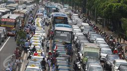 Bus APTB terlihat diantara kendaraan yang terjebak macet di tol dalam kota dan Jalan Gatot Subroto, Jakarta, Selasa (22/3). Ribuan sopir taksi memblokir jalan protokol itu hingga membuat kendaraan lain tidak bisa lewat. (Liputan6.com/Immanuel Antonius)