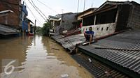 Warga berada di atap rumahnya di kawasan Perumahan Pondok Gede Permai, Bekasi, Jawa Barat, Kamis (21/4). Banjir dengan ketinggian tiga meter yang berasal dari meluapnya Sungai Cikeas. (Liputan6.com/ Immanuel Antonius)