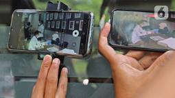 Layar ponsel memperlihatkan gambar Michael Yukinobu Defretes atau Nobu saat melakukan rapid test di Ditreskrimsus Polda Metro Jaya, Jakarta, Senin (4/1/2021). Nobu menjalani pemeriksaan sebagai tersangka dalam kasus video syur bersama Gisella Anastasia atau Gisel. (Liputan6.com/Herman Zakharia)