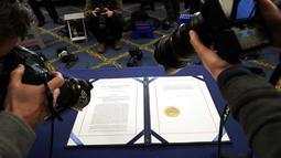 Fotografer mengambil gambar dokumen pemakzulan Presiden Donald Trump sebelum ditandatangani Ketua DPR Nancy Pelosi di Capitol Hill, Washington, Amerika Serikat, Rabu (13/1/2021). Anggota DPR AS memberikan suara 232-197 untuk pemakzulan Trump. (AP Photo/Alex Brandon)