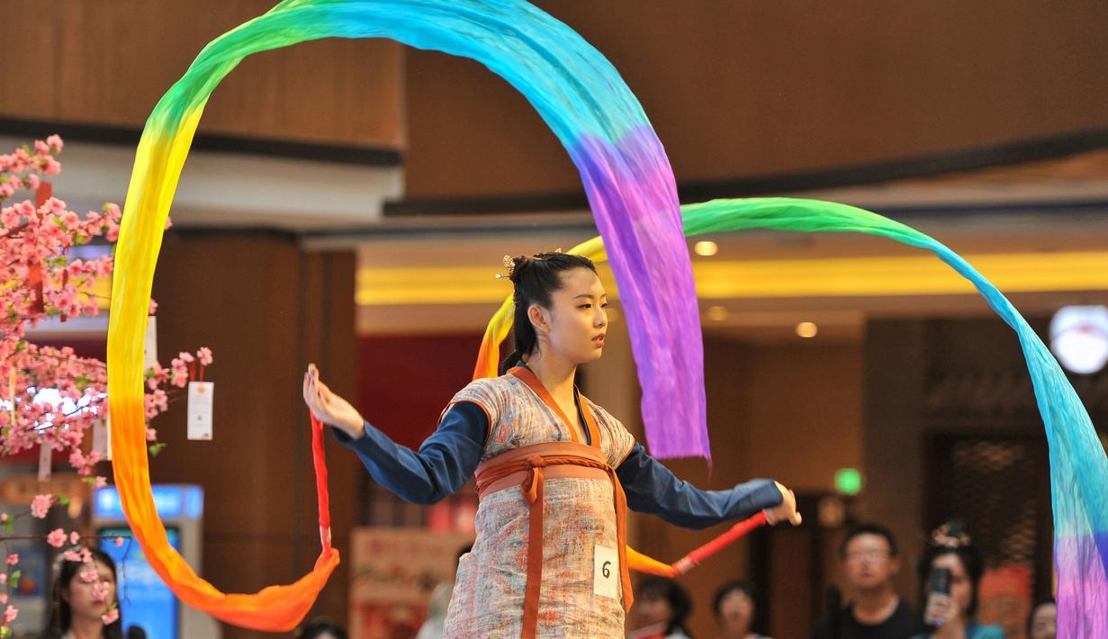 """Seorang peserta mengambil bagian dalam peragaan busana """"hanfu"""", pakaian tradisional khas China di kota Shenyang, China timur laut pada Minggu (15/9/2019). Hanfu sendiri sebenarnya adalah baju tradisional Cina yang digunakan etnis Han China. (Photo by STR / AFP)"""