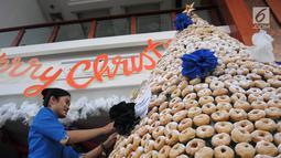 Karyawan menghiasi pohon Natal yang terbuat dari susunan donat di lobby hotel Dafam Semarang, Rabu (12/12). Pohon Natal setinggi 3 meter untuk menyambut Natal tersebut terdapat 2000 buah kue donat. (Liputan6.com/Gholib)