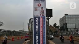 Kendaraan melintasi alat peraga kampanye (APK) yang terpasang di kawasan Depok, Jawa Barat dan Ciputat, Tangerang Selatan, Minggu (18/10/2020). KPU Kota Tangsel dan Depok membagikan sejumlah alat peraga kampanye kepada pasangan calon Pilkada 2020 serentak. (Liputan6.com/Johan Tallo)