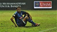 Bek sekaligus kapten tim Arema, Hamka Hamzah, dan sepatu kesayangannya. (Bola.com/Iwan Setiawan)