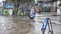 Warga melintasi banjir yang merendam Jalan Abdullah Syafei, Tebet, Jakarta, Kamis (18/2/2021). Hujan deras yang mengguyur sejak pagi tadi menyebabkan aliran Kali Tebet meluap hingga merendam Jalan Abdullah Syafei dengan ketinggian mencapai sepaha orang dewasa. (merdeka.com/Iqbal S Nugroho)