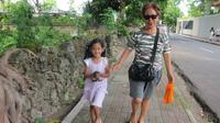Angeline bersama dengan ibu angkatnya Margriet sedang berjalan kaki di Bali. Angeline terlihat sedang membawa anak kucing. Foto ini diberi keterangan bahwa Angeline menemukan anak kucing yang terlantar. (Facebook.com/Find Angeline - Bali's Missing Child)