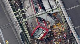 Pandangan dari udara menunjukkan kereta tergelincir setelah menabrak truk di Yokohama, Prefektur Kanagawa, Jepang, Kamis (5/9/2019). Separuh rangkaian kereta anjlok dari rel dan  bagian kaca pada ruang masinis pecah. (JIJI PRESS/AFP)