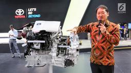 Senior Manager Coodinator Toyota Daihatsu Engineering and Manufacturing (TDEM) Daisuke Itaga menjelaskan kerja mesin mobil hybrid electric vehicle (HEV) Toyota Prius Gen-4 X-Ray cut body yang dipamerkan dalam GIIAS 2019 di ICE BSD, Tangerang, Jumat (19/9/2019). (Liputan6.com/Ferbian Pradolo)