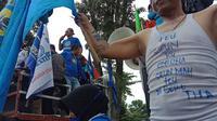 Aliansi Buruh se-Jawa Barat yang terdiri dari 21 serikat pekerja menggelar demonstrasi menolak pengesahan Omnibus Law Rancangan Undang-Undang (RUU) Cipta Kerja di depan Gedung Sate, Kota Bandung, Senin (16/3/2020). (Liputan6.com/Huyogo Simbolon)