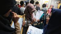 "Pencari kerja menyiapkan dokumen saat Job Fair di Istora GBK, Jakarta, Rabu (19/9). Job Fair bertajuk Jakarta spektakuler ""Job for Career"" diikuti lebih dari 120 perusahaan BUMN, swasta skala nasional maupun internasional. (Liputan6.com/Faizal Fanani)"
