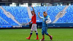 Maskot resmi Piala Eropa 2020, Skillzy dan pemain Rusia, Alexander Erokhin menyapa penonton saat presentasi di Stadion Saint Petersburg, Rusia (27/3). Kota Saint Petersburg akan menyelenggarakan empat pertandingan termasuk pertandingan perempat final selama UEFA Euro 2020. (AFP Photo/Olga Maltseva)