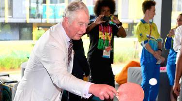 Pangeran Charles memukul bola saat bermain tenis meja selama kunjungannya ke desa atlet Goldwe Common Games 2018 di Gold Coast (5/4). Dalam kunjungannya Pangeran Charles ditemani sang istri Camilla Parker. (AFP Photo/Pool/William West)