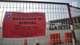 Spanduk penyegelan terpampang di pagar sebuah bangunan proyek reklamasi Pulau D, Teluk Jakarta, Kamis (7/6). Bangunan yang disegel terdiri atas 409 rumah, 212 rumah kantor, dan 313 unit rukan serta rumah tinggal yang disatukan. (Liputan6.com/IqbalNugroho)