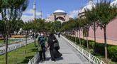 Orang-orang berjalan di depan Hagia Sophia di Istanbul, Turki pada 11 Juli 2020. Hagia Sophia, bangunan berusia 1.500 tahun, saat ini berubah statusnya menjadi masjid. (Ozan KOSE/AFP)
