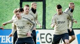 Frenkie de Jong (kiri) dan Klaas Jan Huntelaar (kanan) ikut berlatih jelang menjamu Real Madrid pada leg pertama babak 16 besar Liga Champions di De Toekomst di Ouder-Amstel, Amsterdam, Selasa (12/2). (Robin van Lonkhuijsen/ANP/AFP)