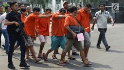 Polisi menggiring para tersangka saat gelar perkara kejatahan wilayah Jabodetabek di Polda Metro Jaya, Jakarta, Jumat (15/3). Para tersangka terjerat kasus begal, pencurian, perampokan hingga jambret. (merdeka.com/Imam Buhori)