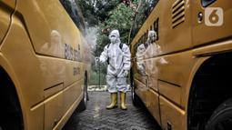 Petugas Kebersihan Bus (PKB) menyemprotkan disinfektan pada bus sekolah di Pool Unit Pelayanan Angkutan Sekolah (UPAS) DKI Jakarta, Kramat Jati, Selasa (5/1/2021). Sterilisasi bus sekolah rutin dilakukan usai digunakan mengangkut pasien terpapar Covid-19 ke RS rujukan. (merdeka.com/Iqbal Nugroho)