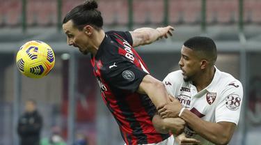 Penyerang AC Milan, Zlatan Ibrahimovic berebut bola dengan bek Torino, Gleison Bremer pada babak 16 besar Coppa Italia 2020/2021 di San Siro, Rabu (13/1/2021) dini hari WIB. Laga terkunci 0-0, AC Milan menang 5-4 atas Torino di babak adu penalti. (AP Photo/Antonio Calanni)